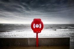 Bright red modern lifebuoy ring water rescue on stormy sea sky, big  ocean waves on coastline. Life saving equipment belt preserver emergency station help prevent drowning dramatic threatening storm