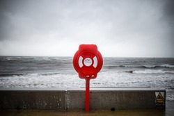 Bright red modern lifebuoy warning on storm sky ocean coastline. Life saving equipment preserver emergency station to help prevent drowning in sea