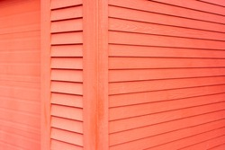 Bright red narrow wooden horizontal clapboard siding on the exterior wall of the building. There's a wide wood trim edge on the corner of the vintage building with a bright red metal garage door.