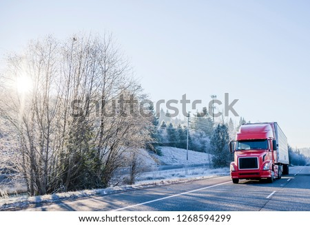Bright red popular big rig bonnet semi truck with refrigerator semi trailer transporting perishable and frozen food cargo on straight winter highway with snow frosty hill trees #1268594299