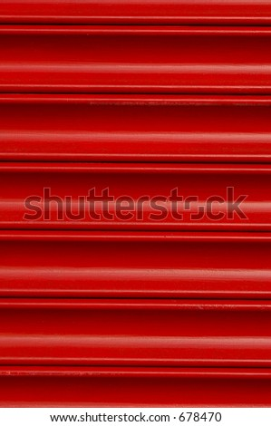 Bright red roller security shutters on a shop front in North Wales.