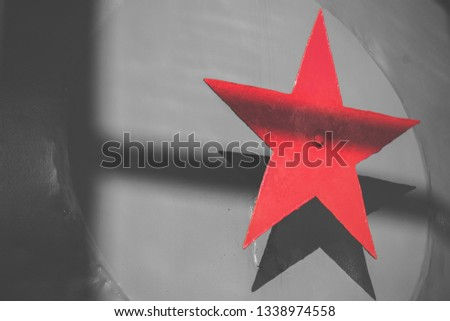 Bright red steel five-pointed star on a gray metallic background. Soviet symbol of communism.