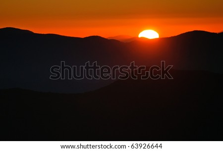 bright red sun rising over a mountain range