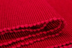 Bright red textured fabric. Red textile background. Ribbed folded fabric.