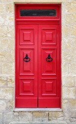 Bright red wooden door of a house with black doorknob rings