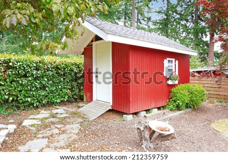 Bright red wooden shed on backyard area