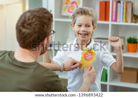 Bright rewarding sign. Contented proud boy being happy with his reward from pleasant elementary school teacher #1396893422