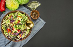 Bright salad of purple cabbage, white cabbage, bell peppers in a dark clay bowl on a dark background. A fresh vegetable salad. Food background. Vegetarian dish. View from above. Copy space