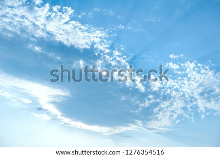 bright saturated blue sky, and a large cloud with rays of the sun.                                #1276354516