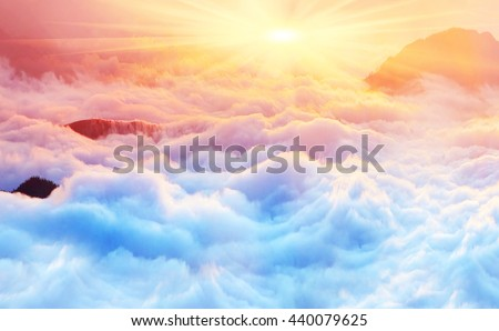 Stock Photo Bright saturated colors dawn above the sea of fog over the tops of the Carpathian is fabulously beautiful panoramic view, illuminated by the golden rays of the rising sun early in the morning