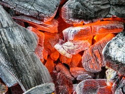 Bright scarlet red-hot charcoal of a bonfire surrounded by smoldering embers