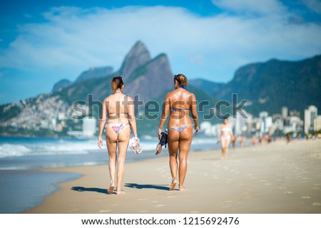 Bright scenic morning view of Two Brothers Mountain towering beyond beachgoers walking on Ipanema Beach in Rio de Janeiro, Brazil