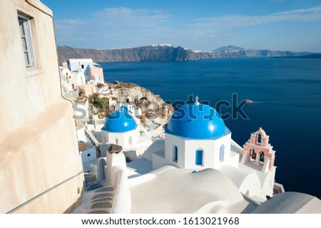 Bright scenic view of sky blue church domes dominating the frame in the Mediterranean hillside village of Oia in Santorini, Greece