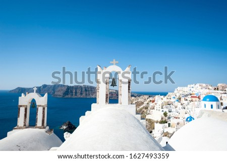 Bright scenic view of whitewashed church domes dominating the frame in the Mediterranean hillside village of Oia in Santorini, Greece