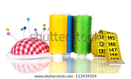 Bright sewing buttons, needle, tape measuring and skeins of thread isolated on white