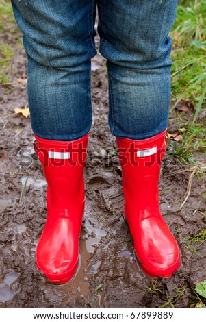 Bright shining clean red rain boots on a girl while she stands in the mud puddle.