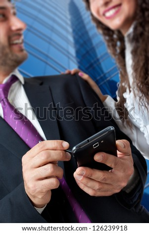 Bright shot of a gourgeous business couple using a smartphone over a skyscraper background