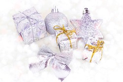 Bright silver Xmas decorations (ribbons, presents, baubles, gift boxes) on white artificial snow background. Christmas and New Year traditional holiday celebration concept