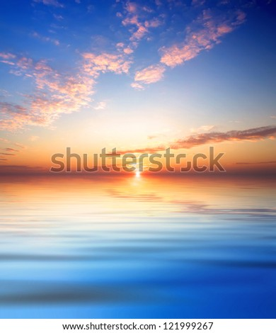 Bright sky and reflection in water during bright sundown.