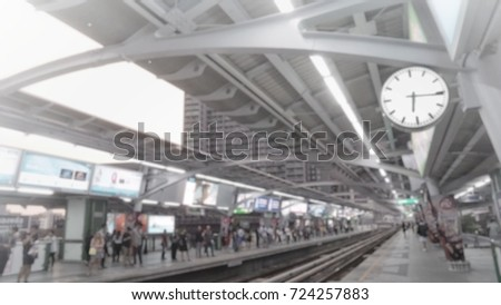 Bright, soft, blurred shot of city sky train platform with crowds waiting in queue for returning home by train after work in evening light  #724257883