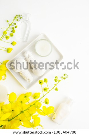 Bright spa background: candles and thai massage herbal bags with bottles and yellow flowers on white. Health, skin treatment concept #1085404988