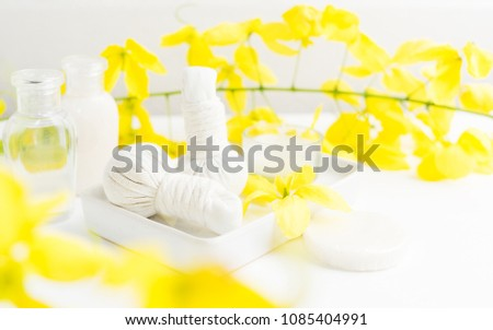 Bright spa background: candles and thai massage herbal bags with bottles and yellow flowers on white. Health, skin treatment concept #1085404991