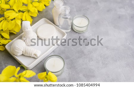 Bright spa background: candles and thai massage herbal bags with bottles and yellow flowers on ????. Health, skin treatment concept? ???? ????? #1085404994