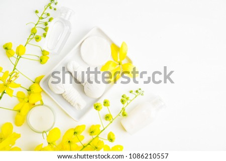 Bright spa background: candles and thai massage herbal bags with bottles and yellow flowers on white. Health, skin treatment concept #1086210557