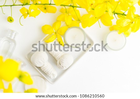 Bright spa background: candles and thai massage herbal bags with bottles and yellow flowers on white. Health, skin treatment concept. Text space #1086210560