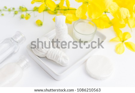 Bright spa background: candles and thai massage herbal bags with bottles and yellow flowers on white. Health, skin treatment concept #1086210563