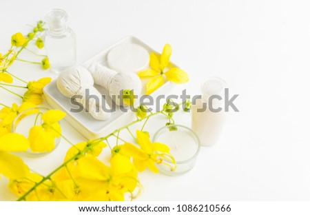 Bright spa background: candles and thai massage herbal bags with bottles and yellow flowers on white. Health, skin treatment concept #1086210566