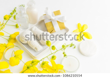 Bright spa background: candles, thai massage herbal bags, shampoo bottles, yellow flowers and gift box with ribbon on white. Health, skin treatment, holiday sale concept. Text space #1086210554