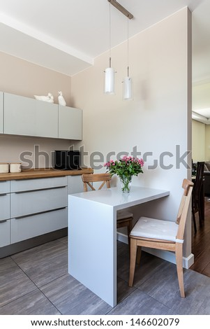 Bright space - a white modern kitchen with dining space