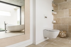 Bright spacious bathroom with sandy tiles and white furniture