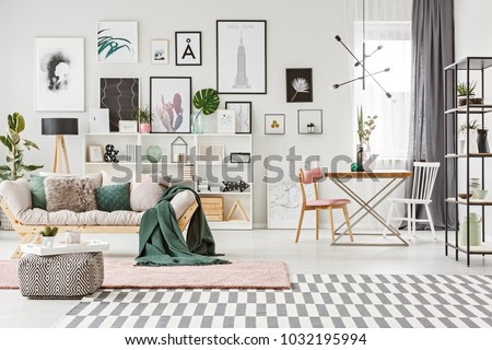Bright spacious living room interior with table standing next to the window and fresh plants