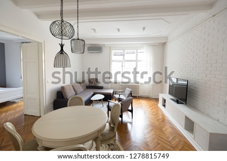Bright spacious living room with chairs table inside #1278815749