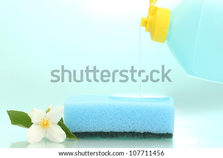 bright sponge and flower  with dish washing liquid on blue background