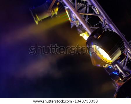 Bright spotlights shining through stage smoke, scaffolding spotlight. #1343733338