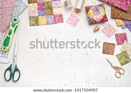 Bright square pieces of fabric, patchwork tools, sewing equipment, traditional quilting, space for text