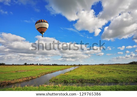 Bright striped balloon flies over the flat plain that is crossed by narrow water channels