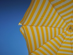 bright striped white and yellow beach umbrella covers from the hot sun