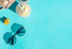 Bright summer beach vacation or travel lifestyle concept frame with lemonade, a straw bag, sunglasses on the blue backfround. Top view. Copy space
