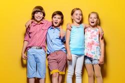 Bright summer children. Group of joyful children posing together over bright yellow background.