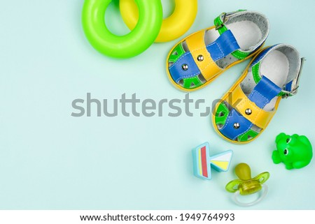 Bright summer children's shoes (sandals), educational toys for the baby (pyramid rings, a boat figure, a rubber frog), a pacifier on a blue background. Space for the text. Children's background. ストックフォト ©