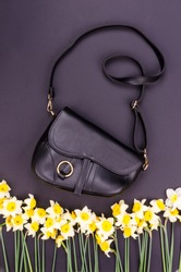 Bright summer fashion ladies accessories. Stylish black leather handbag or flap bag on a grey background with narcissus or daffodil flowers on the edge. Top View. Flat Lay. Copy Space. Mock up