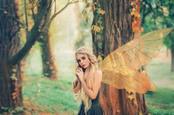 bright summer photo mysterious forest fairy fell in love with prince, girl with puppet happy face, blond long hair and blue eyes, lady angel in green dress peeps modestly interest. Yellow trees.