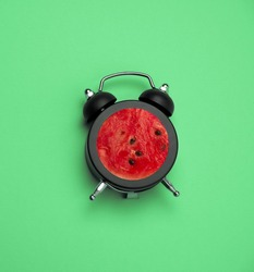 bright summer square poster vintage  black alarm clock with watermelon inside art collage on a green background