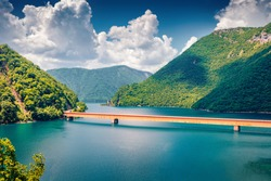 Bright summer view of Pivsko lake with bridge. Picturesque morning scene of canyon of Piva river, Pluzine town location, Montenegro, Europe. Beautiful world of Mediterranean countries.
