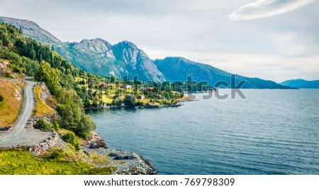 Bright summer view of typical Norwegian village on the shore of fjord. Traveling concept background.   - Shutterstock ID 769798309