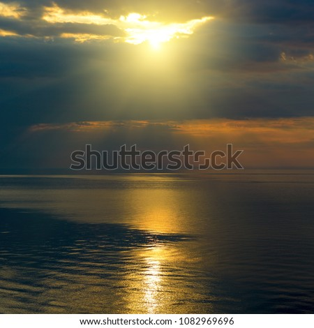 Bright sun in black clouds over ocean with sun track.